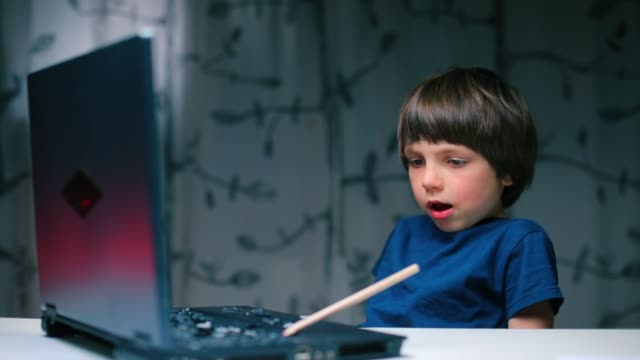 The boy sits at a table with a laptop and breaks off a key with a pencil.