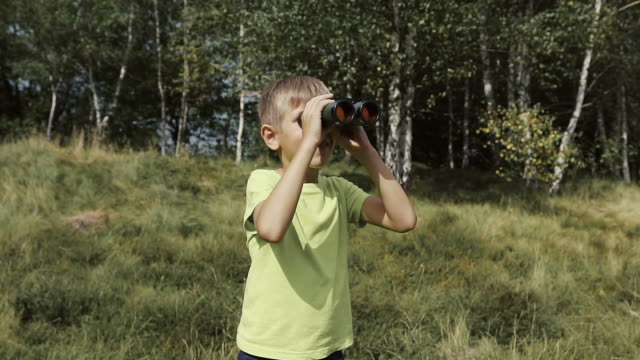 The boy stands on the top of the mountain and looks at the binoculars