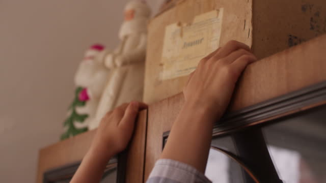 der junge nimmt eine alte schachtel aus dem schrank - dachboden stock-videos und b-roll-filmmaterial