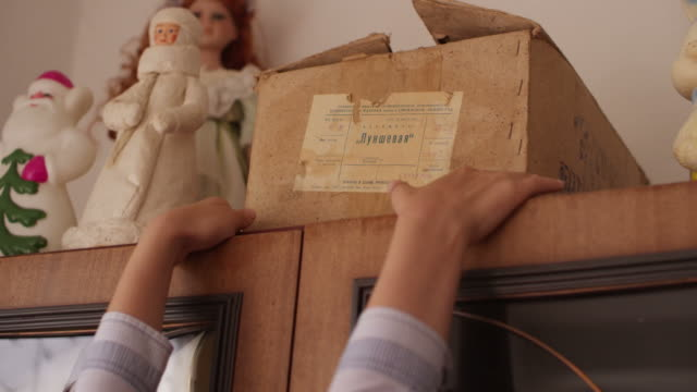 The boy takes an old box from the cupboard video