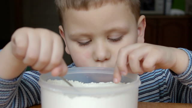 the boy touches the flour and smiles and thumb up video
