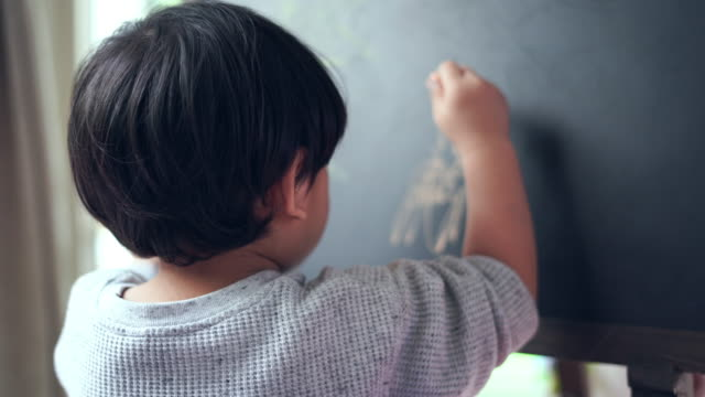 The boy uses chalk to draw on the black board. video