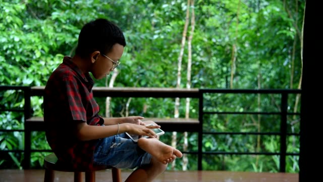 The boy using tablet and sitting near balcony at home in rainy day.