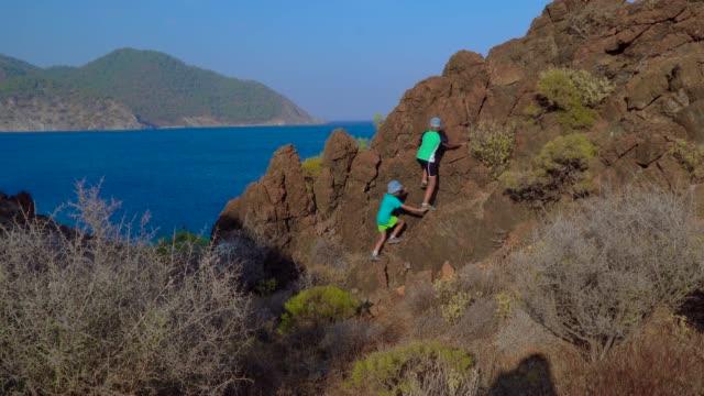 vídeos y material grabado en eventos de stock de los chicos suben a la roca en las orillas del mar mediterráneo - escalada en rocas