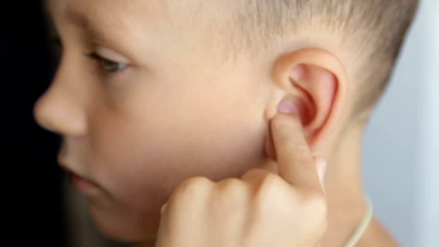 The boy's finger massages the left ear Child's face on the left side, ear close-up ear stock videos & royalty-free footage