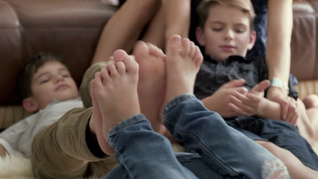 The boys leaned their feet against each other and fooled around The boys leaned their feet against each other and fooled around. The boys are laying on the floor and have fun together. Their brothers sits near them and observes after them. The children are smiling on the background. leaning stock videos & royalty-free footage