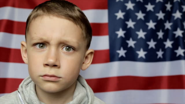 the boy's portrait against the background of the american banner. close up - solo bambini maschi video stock e b–roll