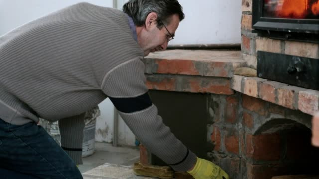 The bricklayer decorates the fireplace with yellow sandstone.