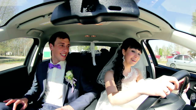 The bride and groom have fun behind the wheel of car. Wedding The bride and groom  have fun behind the wheel of car. Wedding. newlywed stock videos & royalty-free footage