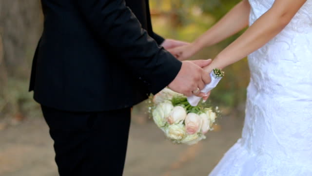 The bride and groom stand nearby and hold hands