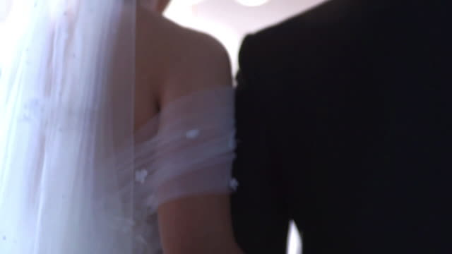 the bride and groom walk arm in arm in the wedding ceremony indoors. - young couple wedding friends video stock e b–roll