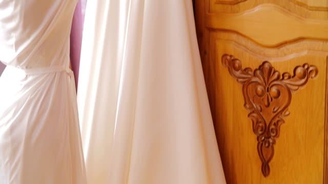 vídeos de stock, filmes e b-roll de a noiva abraçando o vestido de casamento e sorrindo na sala - tule têxtil