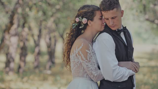 The Bride Hugs the Groom from the Back on the Background of the Forest Landscape. Happiness. Enjoyment. Just married