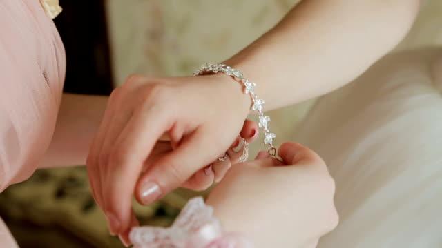 the bride wears wedding jewelry, put bracelet on wrist - браслет стоковые видео и кадры b-roll