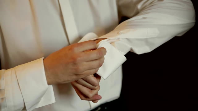 the bridegroom is wearing a wedding shirt, a tie, a jacket - manica video stock e b–roll