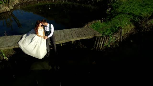 vídeos de stock e filmes b-roll de the brides sit near the lake on a small bridge in the park - man admires forest