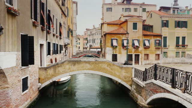 The bridge is through a narrow canal in the center of Venice. Typical architecture of Venice video
