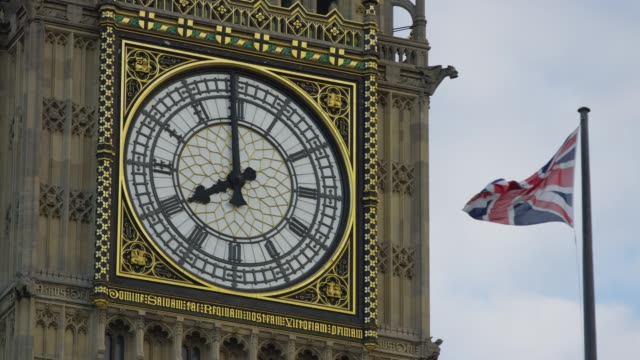 The British flag waving near the Big Ben Clock Tower The British flag waving near the Big Ben Clock Tower instrument of time stock videos & royalty-free footage
