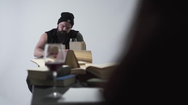 the brutal bearded man and young unrecognizable woman in black clothes sitting at the long table - top nero video stock e b–roll