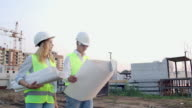 istock The builder and architect man and woman are discussing the construction plan of the modern business center standing near construction site. They go to the building 1169027818