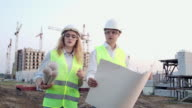 istock The builder and architect man and woman are discussing the construction plan of the modern business center standing near construction site. They go to the building 1169029234