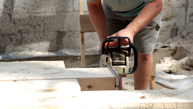 The builder cuts a wooden beams for building a roof. video