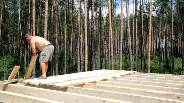 The builder lifts the rafters onto the roof and stacks them on the beams. video