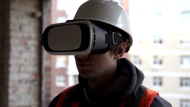 The builder uses virtual reality glasses on one of the floors of a high-rise building - vídeo