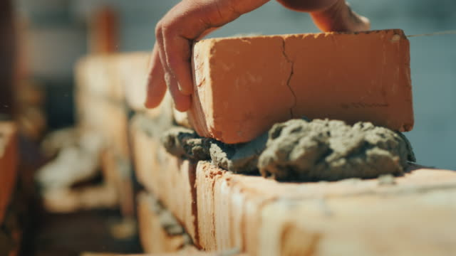 the builder's hand puts the brick in the masonry of the wall - mattone video stock e b–roll