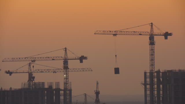 The building with construction cranes against the sunset