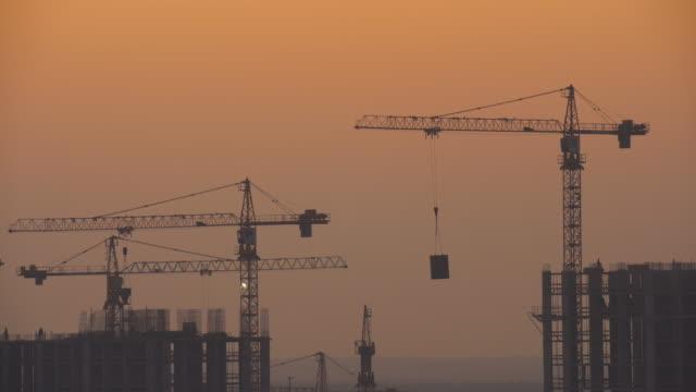 vídeos y material grabado en eventos de stock de el edificio con grúas de construcción contra la puesta de sol - grúa