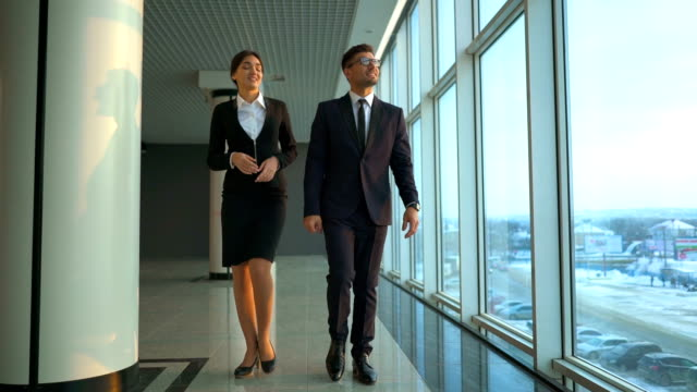 The business couple walking along the window. slow motion