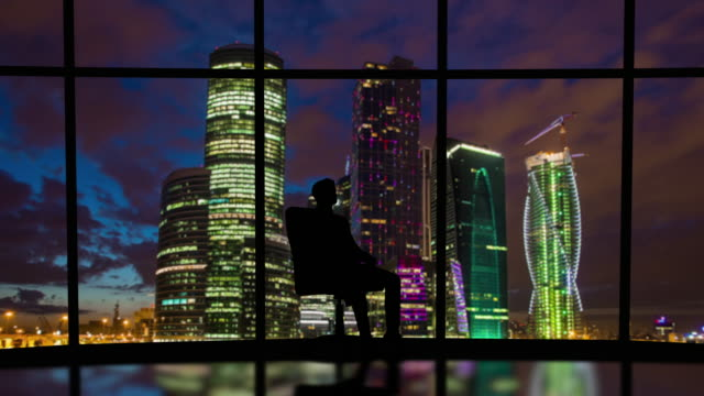 the business man is spinning in the chair on the night city background - man look sky scraper video stock e b–roll