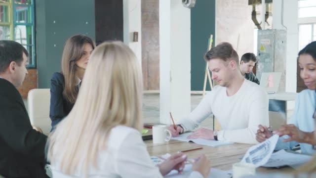 ビジネスチームはオフィスの大きなテーブルで会合を開きます。スタッフの一人が起きて出て行く。クリエイティブなオフィスインテリア。コワーキングスタートアップチーム。オフィスワ� ビデオ