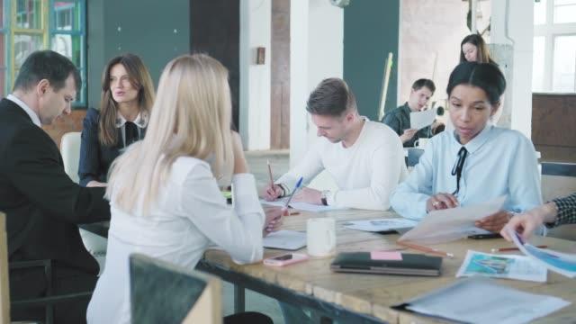 ビジネスチームはオフィスの大きなテーブルで会合を開きます。オフィスは大騒ぎします。クリエイティブなオフィスインテリア。コワーキングスタートアップチーム。オフィスワーカー ビデオ