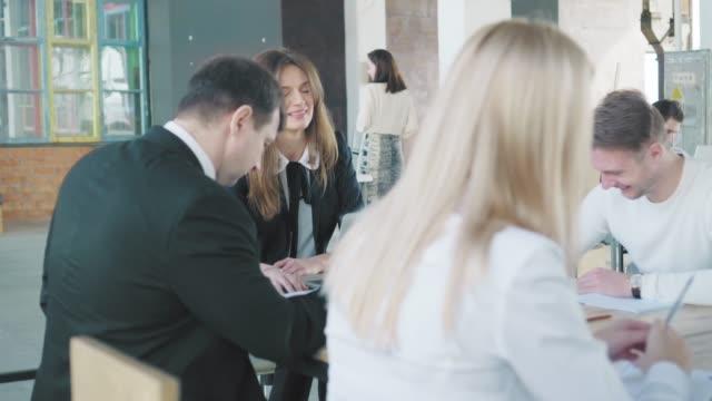 ビジネスチームはオフィスの大きなテーブルで会合を開きます。クリエイティブなオフィスインテリア。コワーキングスタートアップチーム。オフィスワーカー ビデオ