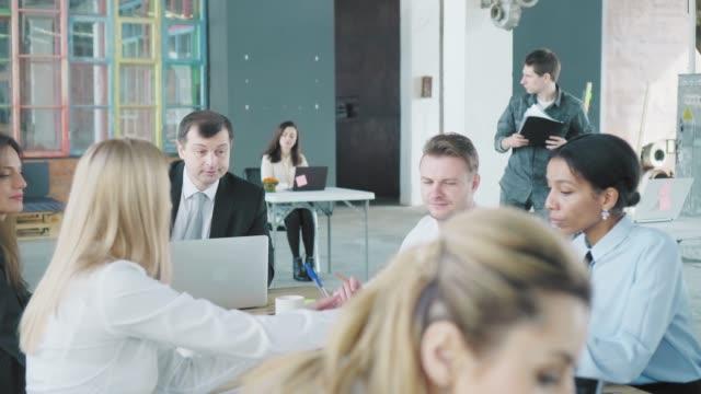 ビジネスチームはオフィスの大きなテーブルで会合を開きます。クリエイティブなオフィスインテリア。コワーキング。オフィスライフ ビデオ