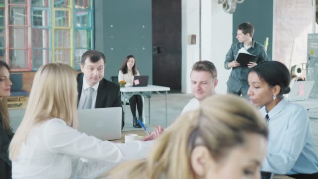 Das Business-Team trifft sich an einem großen Tisch im Büro. Kreative Büro-Interieur. Co-Working. Büroleben – Video