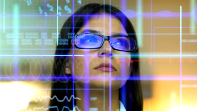the business woman in glasses looking to the screen on the hologram background - progettare video stock e b–roll