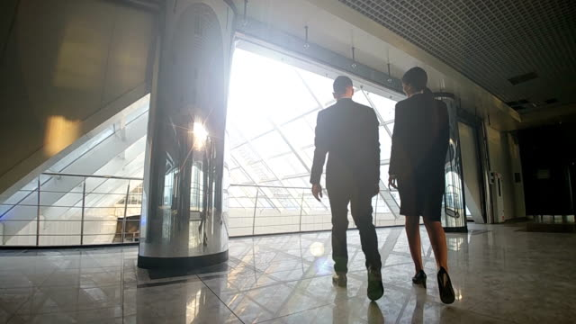 The businessman and a businesswoman walking in the office center. slow motion