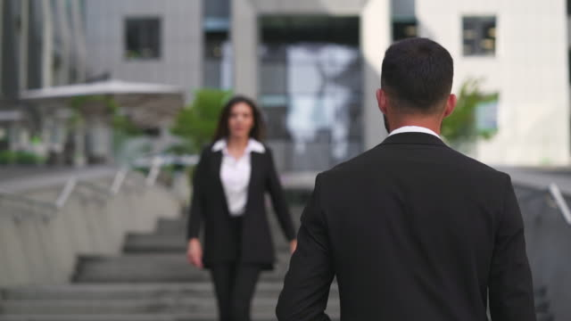 the businessman and businesswoman meet each other outdoor - occhiata laterale video stock e b–roll