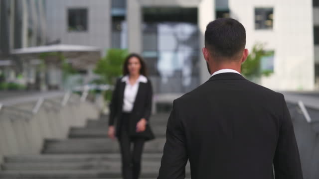 the businessman and businesswoman meet near business office. slow motion - occhiata laterale video stock e b–roll
