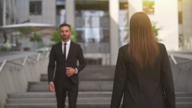 stockvideo's en b-roll-footage met de zakenman en zakenvrouw ontmoeten elkaar in de buurt van het business office - flirten