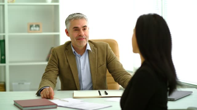 The businessman interviews a woman in the office room