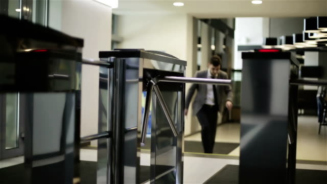The businessman is passing through a turnstile.