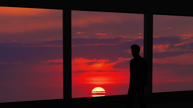the businessman is standing near the panoramic window against the sunset - man look sky scraper video stock e b–roll