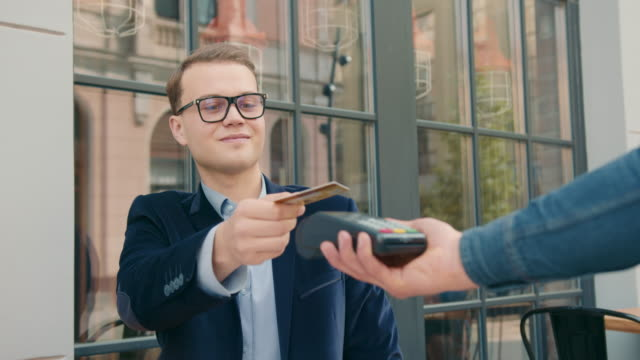 the businessman is taking out a credit card and paying for the order via a contactless payment terminal. lunch break. 4k - credit card filmów i materiałów b-roll