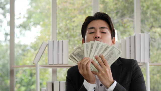 The businessman kisses the dollar with pride in the success of selling life insurance