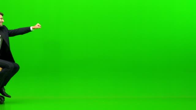 affärs mannen som spelar på kontors stolen på den gröna bakgrunden - superhjälte isolated bildbanksvideor och videomaterial från bakom kulisserna