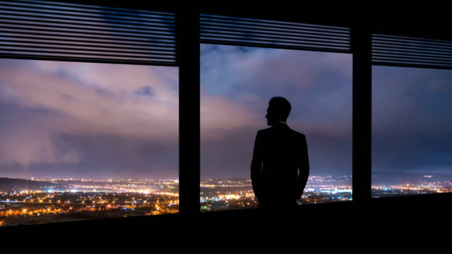 the businessman stand near the window on night city background. time lapse - guardare il paesaggio video stock e b–roll